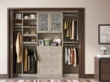 Reach in Closet with Glass Fronted Display Cabinet and Light Brown Shelves Drawers and Closet Rods
