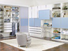 White and Blue Walk in Closet With Cabinets Shelves Closet Rods Sliding Doors and Fold Out Desk