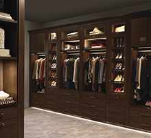 Dark Wood Walk in Closet with Dresser Drawers and Lighted Glass Door Shelving Cubbies and Closet Rod Space