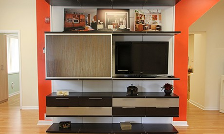 Black Entertainment Center with Floating Shelves and Cabinets White Backing and Light Brown Accent Drawers and Siding Door