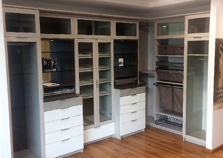 California Closets Guadalajara showroom interior multiple cubbies with and without clear glass doors open shelving clothing hanging spaces with and without clear glass doors and drawers.