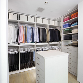 Walkin Closet with White Shelving Drawers Closet Rods Storage Baskets and Island Dresser