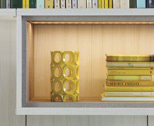 Close Up of Off White Library Shelf with Grey Trim Built in Lighting and Light Wood Backing