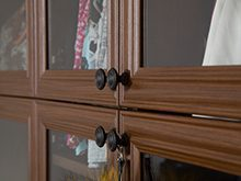 California Closets Client Stories Gallery Dark Brown Boutique Walk in Closet Close up of Glass Door Cabinets