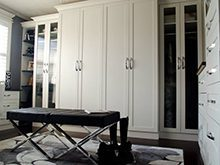 White Walk in Closet with Wardrobe Built in Desk Cabinets with Glass Doors and Black Stand Alone Bench
