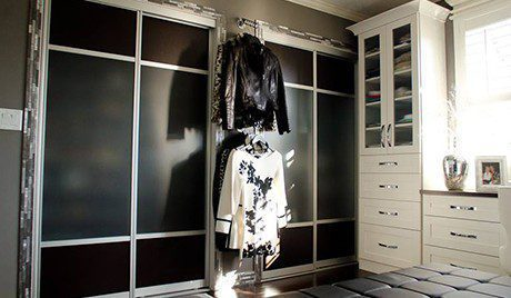 Walk in Closet with White Shelving Black and Metal Sliding Doors Cabinets with Glass Door and Black Stand Alone Seating Bench