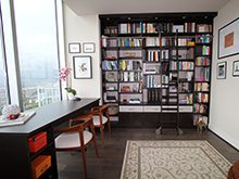 Office Library with Black Stand Alone Desk Built in Shelving and Rolling Latter and High Gloss White accent Drawers