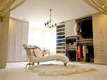 Mottled White Walk in Closet with Lounge Chair Shelving Cabinets and Gold Accented Closet Rods and Handles