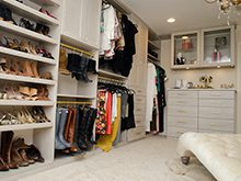 Modeled White Walk in Closet with Lounge Chair Shelving Cabinets and Gold Accented Closet Rods and Handles