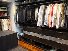 Dark Brown Walk in Closet With Hanging Clothes and Floor Level Shoe Cubbies