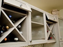 Close Up of White Wood Grain Pantry Storage With X Design Wine Cubbies and Etched Glass Door Cabinets