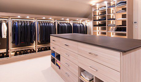 Light Wood Walk in Closet with Shoe Racks Hanging Clothes Built in Lighting and Stand Alone Dresser With Dark Brown Top
