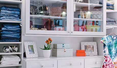 Close up of White Closet Shelving Dresser Drawers and Cabinets with Glass Doors