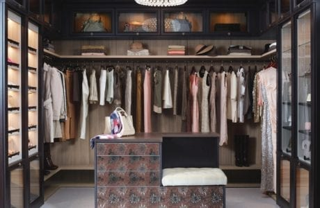 LIght Brown Walk in Closet with Dark Brown Fronting Closet Rods Shelves and Lighted Display Cabinets