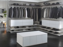 Light Grey and White Walk in Closet With Shelving Closet Rods Drawers and Storage Island