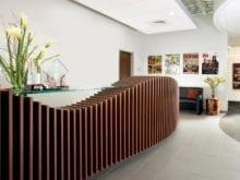 Reception desk with lago roman walnut finish and glass countertop