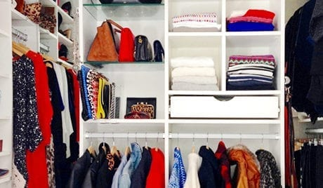 Close Up Image of Walk in Closet with White Shelving and Closet Rods