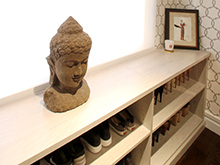 Liberte Chan Client Story Walk In Closet with Light Brown Shoe Rack and Buddha Centerpiece