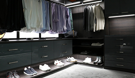 Black Walk in Closet with High Gloss Cabinets and Drawers Built in Lighting and Wood Grain Backing