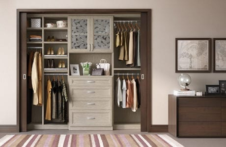 Reach in Closet with Grey Wood Grain Shelving Drawers and Cabinets with Decorative Glass Doors