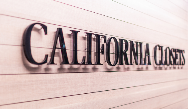 Metal California Closets logo on wood panel wall at Sayville Showroom