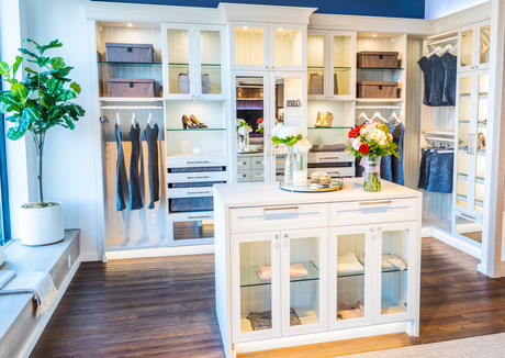 California Closets showroom in Sayville with mock walk-in closet with white island dresser in center surrounded by shelving