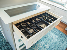 Jewelry drawer organizer held in a cream colored cabinet