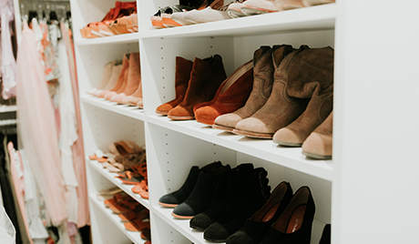 Shoes organized by color held in white shelves