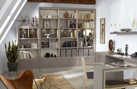 Office Space with Grey Shelving Cabinets L Shaped Desk Built in Lighting and Light Wood Accents