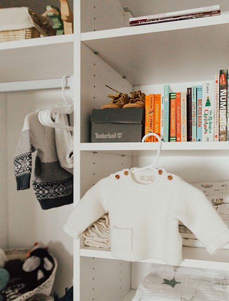 A baby shirt hanging on display amongst white shelving with various organized items