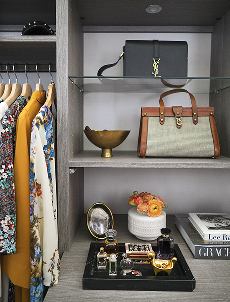 Light grey woodgrain shelving displaying purses and perfume for California Closets client Anna Bond