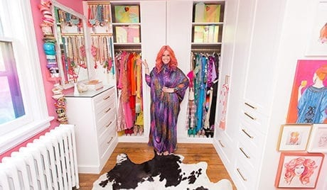 California Closets client Tiffany Pratt stands smiling in her newly renovated colorful closet