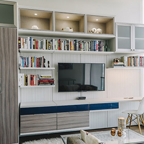Entertainment Center with White Floating Shelving and Display Cubbies Dark Wood Cabinets and Dark Blue Drawers