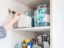 Cleaning supplies organized in cream colored shelves