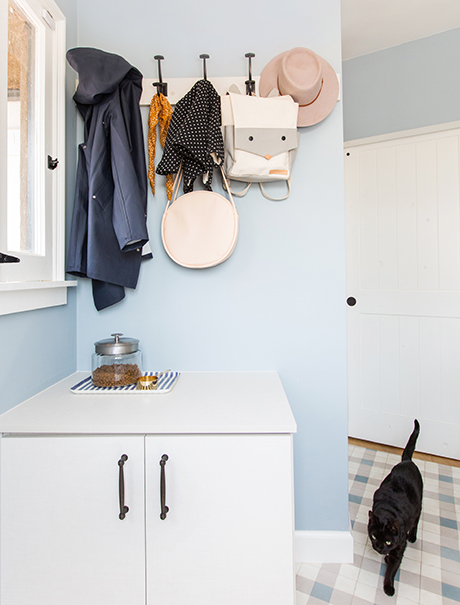 Accessories hanging on coat hooks above a custom white cabinet