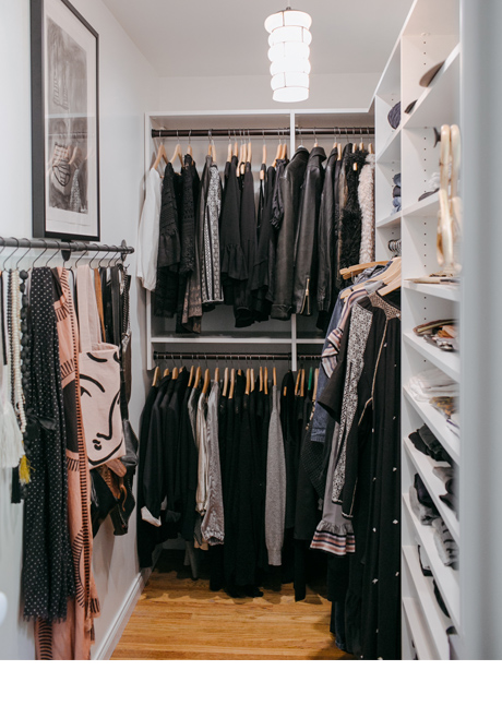 Narrow white walk in closet with dark clothes and accessories hanging up