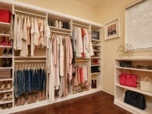 Organized clothing hanging from brass poles in a white closet unit