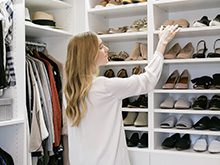 California Closets client Kimberly Lapides placing shoes into her new organized closet