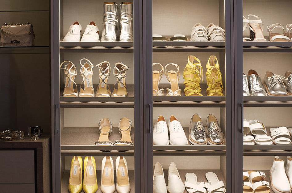 Shoe Closet with shelves behind glass doors, illuminated with LED lights.