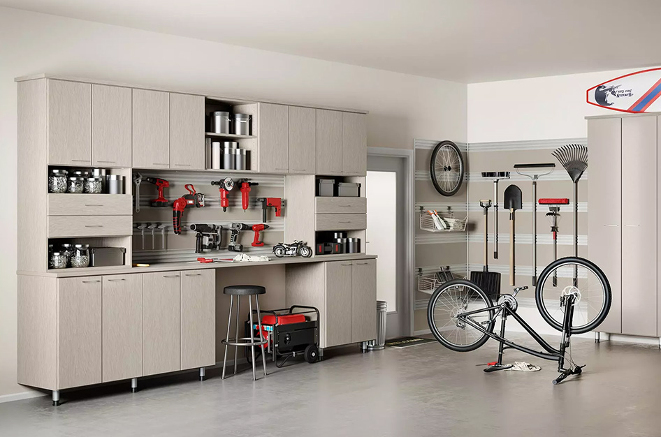 Furnished garage with a workbench, cabinets, and wall space for mounted tools.