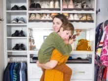 California Closets client Katie Hinz Zambrano holding her son while standing in her custom walk in closet
