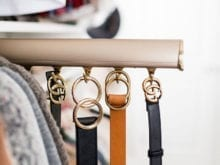 Pull out rack holding belts in fashion blogger Brittany Sjogren's walk in closet by California Closets