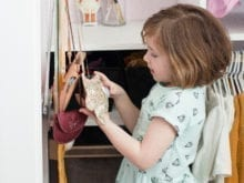 Child plays with small handbags hanging from white door