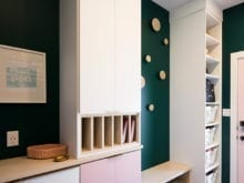 Tall white shelving flanking wooden bench in green room