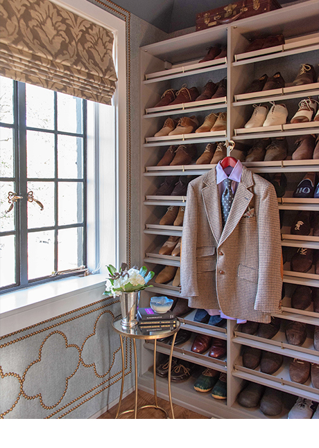 Shelving for dress shoes with coat hanging inside walk-in closet designed by Amber Colo and Sarah Smith