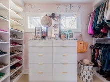 White dresser with metal drawer handles in walk-in closet with shelving for shirts and shoes