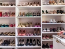 Side view of walk-in closer with white shelving for multicolored shoes
