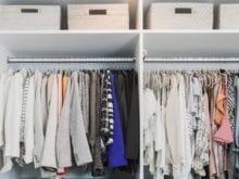 White storage boxes above hanging shirts