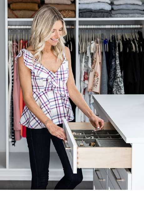 Kristen Lawler looking at custom designed drawers in walk-in closet