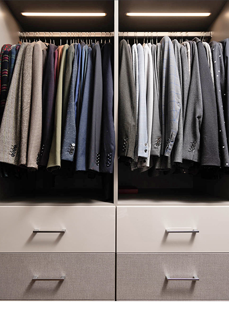 Suit jackets displayed from hanging rods and custom cabinetry for Brad Goreski